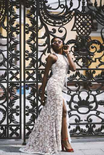 woman wearing white floral sleeveless side slit maxi dress standing beside black metal gate